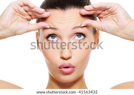 Close-up female face with a big wrinkles on her forehead - isolated on white - stock photo