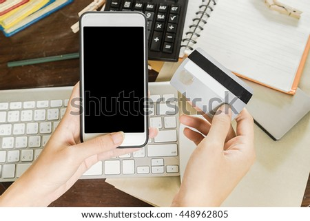 Close up female hands holding a credit card and using smart phone for online shopping, Low light, selective focus on hand, can be used for e-commerce, business and technology concept, Vintage tone - stock photo