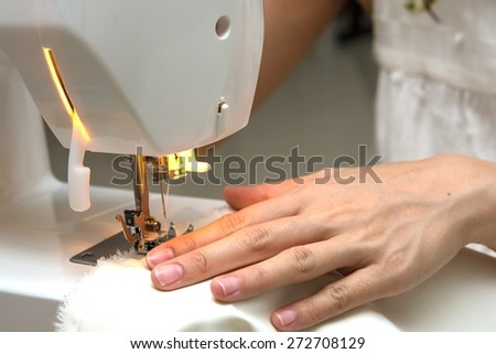 Close-up female hands sewing fabric on sewing machine