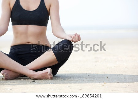 Close up female in yoga lotus position at the beach - stock photo