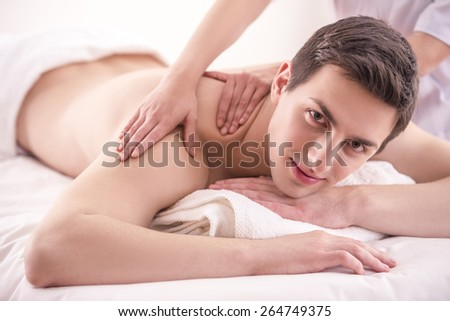 Close-up. Female masseur doing massage on male in the spa salon. - stock photo