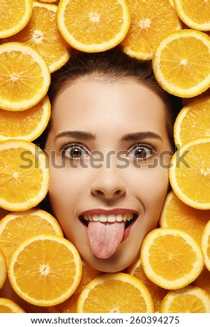 Close up female model face with make up in the middle sliced oranges - stock photo