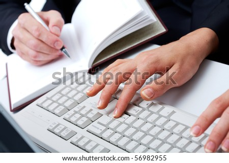 Close-up female?s hands touching keys of computer on background of businessman making notes - stock photo