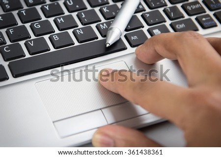 Close up finger touch on laptop touch pad - stock photo