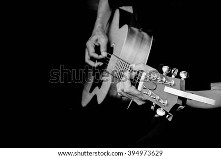 Close up fingers of man playing acoustic guitar in black and white filter