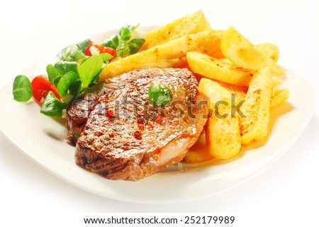 Close up Flavored Grilled Tender Meat with Potato French Fries on White Plate with Herbs. - stock photo