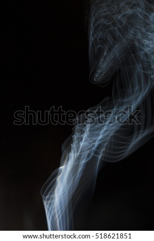 Close up fluffy puffs of smoke and fog backlit creating system of abstract curves and lines isolated on black background. Creative art macro photography in backlight.