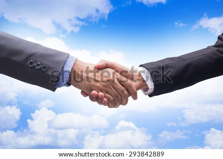 close up focus business man handshake on blurred blue sky background:official adult man in suit outstretched arm hands shaking togetherness for agreement in promise concept:partner/colleagues concept. - stock photo
