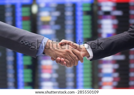 close up focus business man handshake on stock trade board background:two adult man in suit outstretched arm hands shaking togetherness for agreement in promise concept:partner and colleagues concept - stock photo