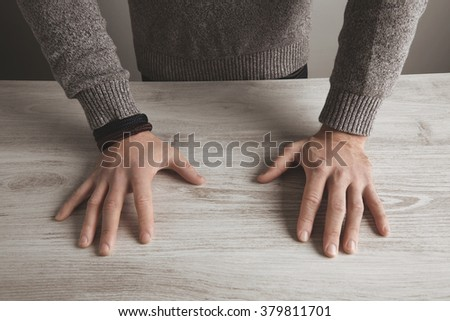 Close up focus detailed image of unrecognizable brutal man hands in neutral grey sweater on white wooden table, isolated. Presentation concept.