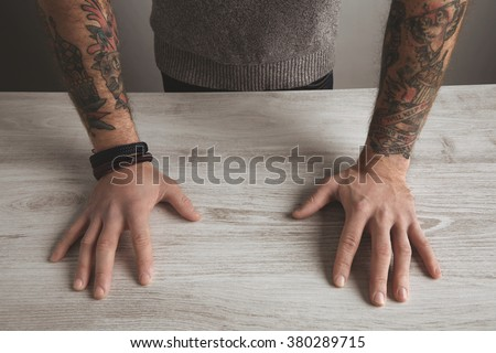 Close up focus detailed image of unrecognizable brutal man sleeve old school tattooed hands in neutral grey sweater on white wooden table, isolated. Presentation concept.