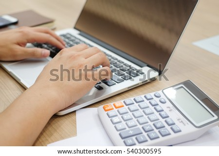 close up focus man hand type work on notebook mobile portable device on office desk with calculator and book:business and technology concept.