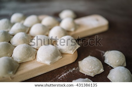 Close up focus ready tasty raviolis or dumplings filled with minced meat on flour on wooden board - stock photo