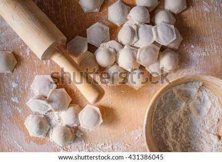 Close up focus ready tasty raviolis or dumplings filled with minced meat on flour wooden board - stock photo