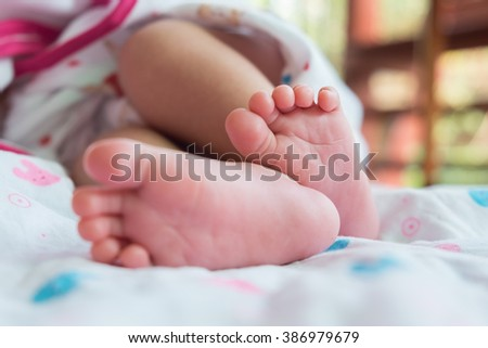 Close up foot a little baby is lying sweet dream. Asian baby. - stock photo