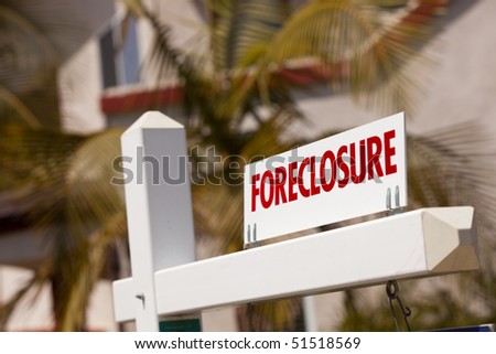 Close-up Foreclosure Real Estate Sign in Front of House. - stock photo