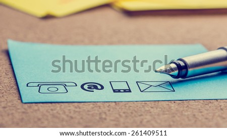 Close up Four Different Contact Icons Printed on a Light Blue Paper with Pen on Top of the Table, Toned Retro Effect. - stock photo
