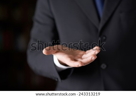 Close-up fragment of a man in a business suit holding a open palm in front of him, shallow depth of field composition - stock photo