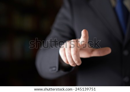Close-up fragment of a man in a business suit holding a pointing finger in front of him, shallow depth of field composition - stock photo