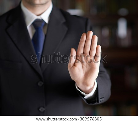 Close-up fragment of a man in a business suit showing an open palm stop sign gesture, shallow depth of field composition - stock photo