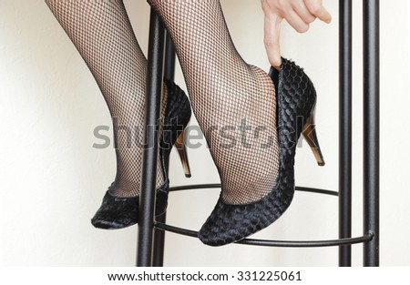 Close-up fragment of female legs in fishnet stockings and heels isolated on a white background - stock photo