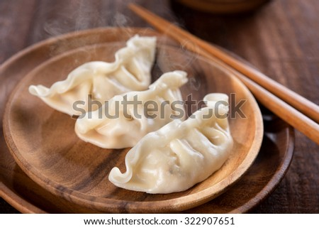 Close up fresh boiled dumplings with hot steams on wood plate. Chinese food on rustic old vintage wooden background.  - stock photo
