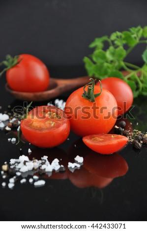 Close up fresh cherry tomato on black background - stock photo