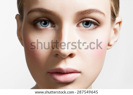 Close-up fresh face model with perfect clean skin and rosy cheeks on a white background - stock photo
