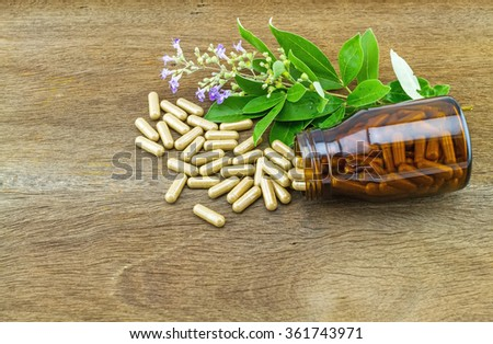 Close up fresh flower Vitex trifolia Linn or Indian Privet with green leaf  is herb in Thailand and drug pill in black bottle on wooden background - stock photo