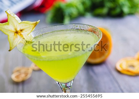 Close up fresh green apple soft lemonade in a glass on a wooden table with decorations focus on different parts of the glass - stock photo