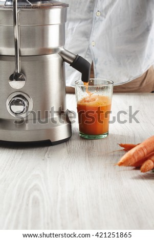 Close up fresh juice pours from steel professional juicer to transparent glass in cafe shop. Healthy drink for breakfast from fresh organic carrots, lying on wooden table near - stock photo