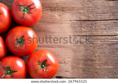Close up Fresh Organic Red Tomatoes Placed on Top of a Wooden Market Table with Copy Space for Texts. Captured in High Angle View. - stock photo
