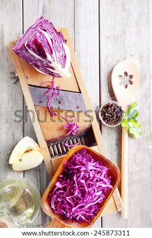 Close up Fresh Purple Cabbage and Apple Salad Ingredients on Wooden Table with Shredder and Wooden Ladle. - stock photo