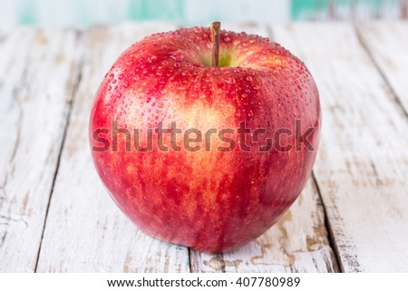 Close up fresh red apple on wooden table background - stock photo