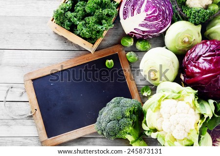 Close up Fresh Salad Vegetables from the Farm on Wooden Table with Black Chalkboard. Emphasizing Copy Space. - stock photo