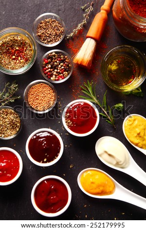 Close up Fresh Various Spices and Sauces on the Black slate kitchen Table - stock photo