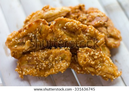 Close up fried bananas sprinkled sesame tasty traditional food which is placed on a pile of bamboo flooring. - stock photo