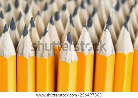 Close up front image of stacked pencils with focus on tip of centered pencil - stock photo