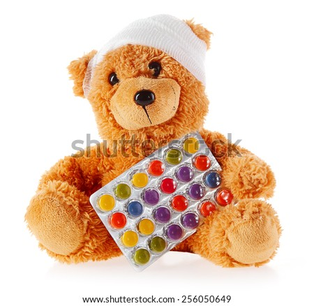 Close up Front View of Bandaged Brown Teddy Bear with Foil Blister Pack of Tablets, Isolated on White Background. - stock photo