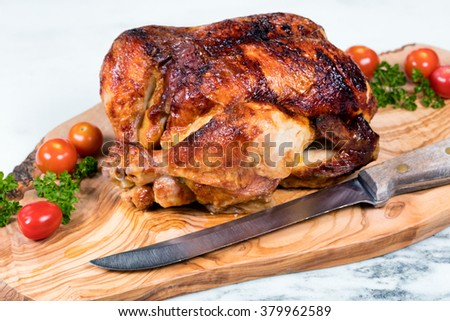 Close up front view of barbecued chicken with vegetables, herbs and large cutting knife on wooden server with white marble underneath. Selective focus on upper front leg of chicken.  - stock photo
