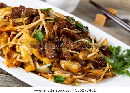 Close up front view of freshly cooked spicy beef, bean sprouts, onion, and tofu with parsley as garnish and chopsticks in holder on rustic wood.  - stock photo