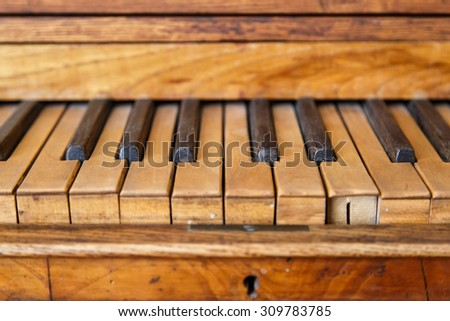Close up front view of old wooden piano with brown and black keys. - stock photo
