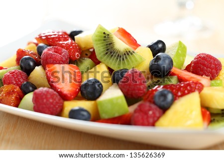 close up fruit salad strawberries kiwi pineapple and raspeberries on plate