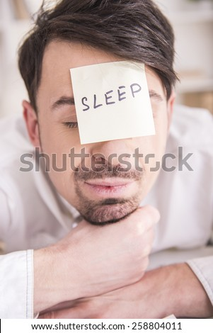 Close-up frustrated young businessman in his office with note on his forehead. He want sleep - stock photo