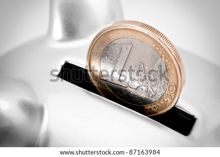 Close-up full frame image of one Euro coin partially inserted into the slot of a silver piggy bank. - stock photo