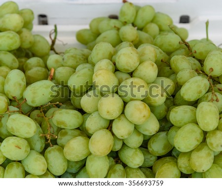 Close-up full frame view of fresh green grapes on display on Styrofoam box for sale at a local fruits market in Singapore. Natural food background - stock photo