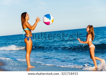 Close up full length portrait of two Young girls playing with inflatable ball on beach. - stock photo