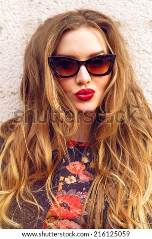Close up funny playful portrait of young woman with gorgeous blonde ginger long curly hairstyle, wearing retro styled cat eye sunglasses and bright lips. Fashion girl making kiss. - stock photo