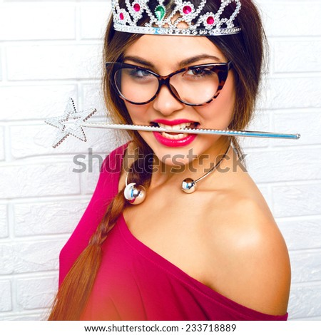 Close up funny portrait of brunette hipster woman, ready for masquerade party wearing sexy fairy costume, stockings, vintage glasses, funny fake crown and holding magic wand in her teeth.  - stock photo