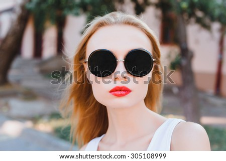 Close up funny portrait of sexy,sensual young pretty girl, wearing cute sunglasses, posing at city center at sunny summer day.Natural daily make-up,windy day,red lips.casual outfit  - stock photo
